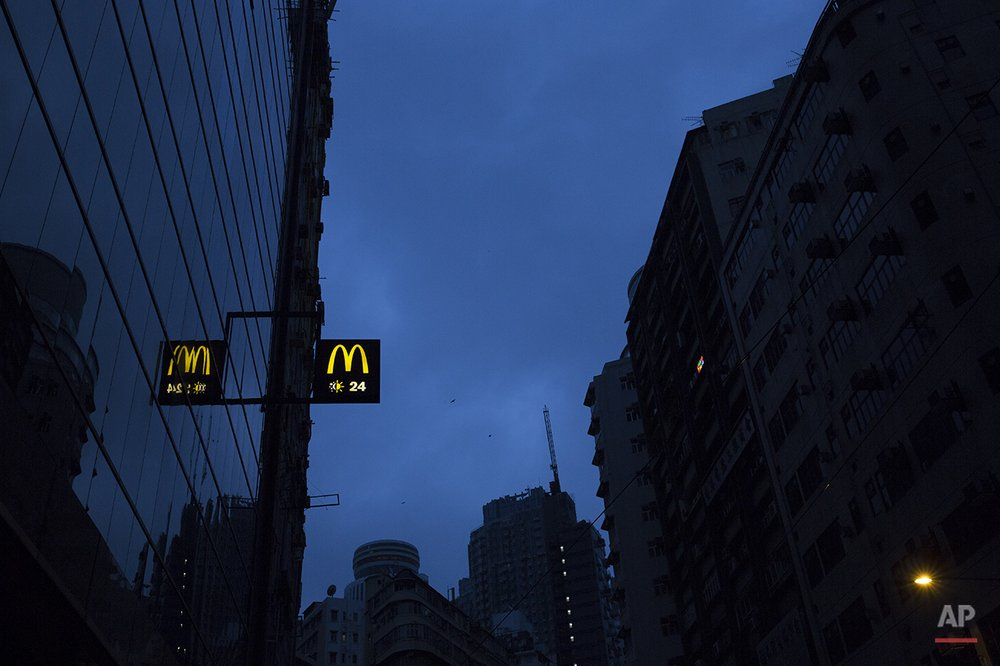 "In this Nov. 12, 2015 photo, a sign of a 24-hour McDonald's branch is seen early morning in Hong Kong. The recent death of a woman at a Hong Kong McDonald's, where her body lay slumped at a table for hours unnoticed by other diners, has focused attention on the city's working poor and homeless people, dubbed ""McRefugees,"" who spend their nights at the fast food outlet's 24-hour branches. (AP Photo/Vincent Yu)"