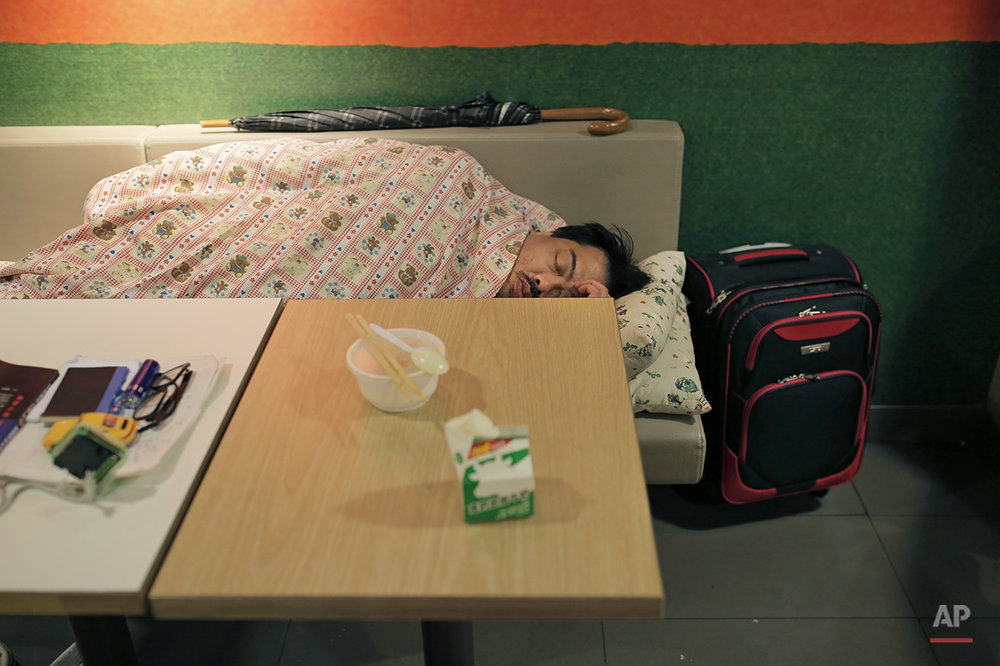 "In this Nov. 9, 2015 photo, a man sleeps with his belongings at night in a 24-hour McDonald's branch at night in Hong Kong. The recent death of a woman at a Hong Kong McDonald's, where her body lay slumped at a table for hours unnoticed by other diners, has focused attention on the city's working poor and homeless people, dubbed ""McRefugees,"" who spend their nights at the fast food outlet's 24-hour branches. (AP Photo/Vincent Yu)"
