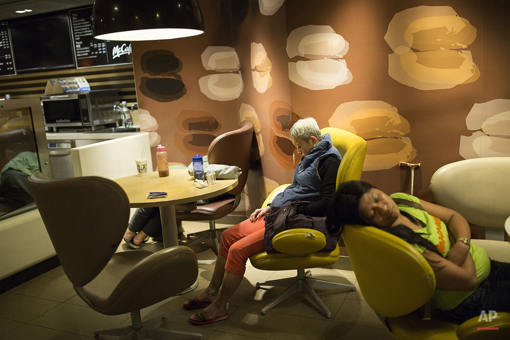 "In this Oct. 29, 2015 photo, a group of people sleep at night in a 24-hour McDonald's branch in Hong Kong. The recent death of a woman at a Hong Kong McDonald's, where her body lay slumped at a table for hours unnoticed by other diners, has focused attention on the city's working poor and homeless people, dubbed ""McRefugees,"" who spend their nights at the fast food outlet's 24-hour branches. (AP Photo/Vincent Yu)"