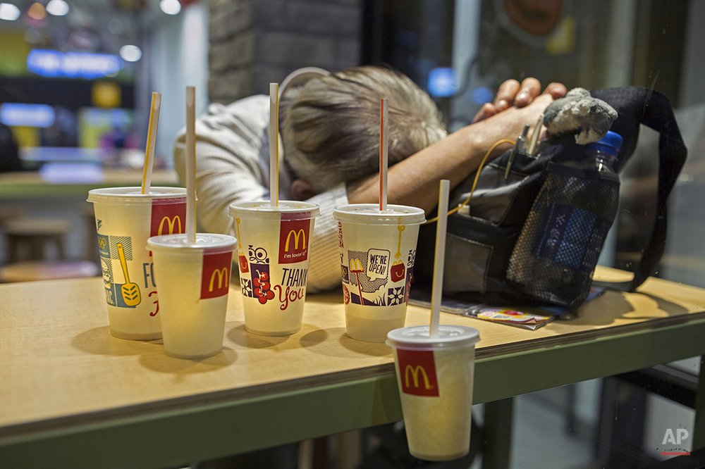 "In this Oct. 29, 2015 photo, a man sleeps with his belongings at night in a 24-hour McDonald's branch in Hong Kong. The recent death of a woman at a Hong Kong McDonald's, where her body lay slumped at a table for hours unnoticed by other diners, has focused attention on the city's working poor and homeless people, dubbed ""McRefugees,"" who spend their nights at the fast food outlet's 24-hour branches. (AP Photo/Vincent Yu)"