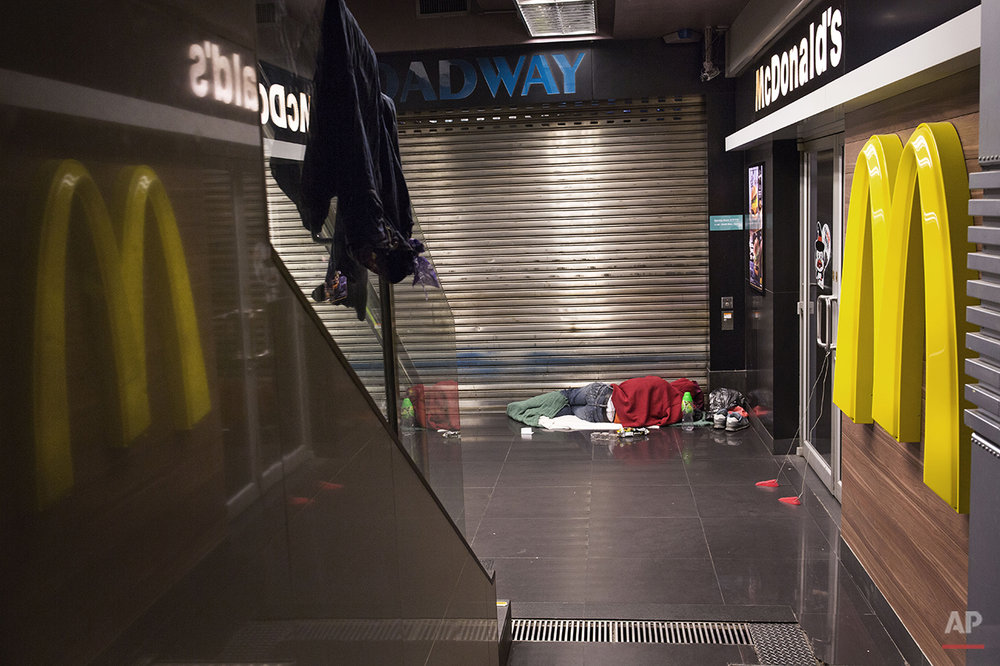 "In this Nov. 5, 2015 photo, a man sleeps with his belongings at night outside a 24-hour McDonald's branch in Hong Kong. The recent death of a woman at a Hong Kong McDonald's, where her body lay slumped at a table for hours unnoticed by other diners, has focused attention on the city's working poor and homeless people, dubbed ""McRefugees,"" who spend their nights at the fast food outlet's 24-hour branches. (AP Photo/Vincent Yu)"