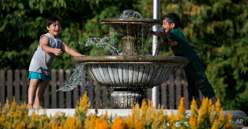In this photo taken on Friday, Sept. 18, 2015, migrant children play at a fountain in Harmica near the Slovenian and Croatian border, in Croatia.  Among the hundreds of thousands of migrants making their way to Europe, there are many families whose young children still play or find something to smile about even after harrowing experiences and long journeys. (AP Photo/Christian Bruna)
