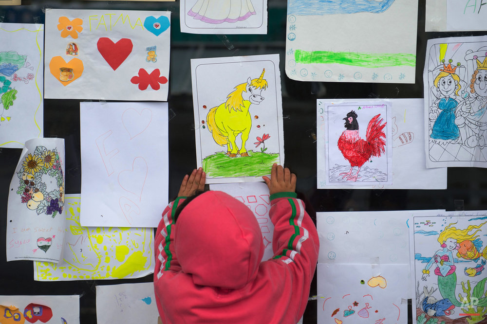 In this photo taken on Thursday, Sept. 24, 2015, a migrant child looks at a unicorn painting during the Muslim holiday of Eid al-Adha in a shelter at a former shopping mall in Graz, about 190 kms (118 miles) south of Vienna, Austria. Among the hundreds of thousands of migrants making their way to Europe, there are many families whose young children still play or find something to smile about even after harrowing experiences and long journeys. (AP Photo/Christian Bruna)