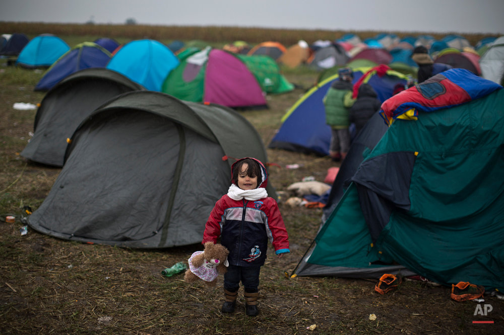 In this photo taken on Thursday, Sept. 10, 2015, syrian refugee child Jana Makkiyeh, 3, whose family comes from Damascus, Syria, holds a teddy bear while standing near her family's tent at a makeshift camp for asylum seekers in Roszke, southern Hungary. Among the hundreds of thousands of migrants making their way to Europe, there are many families whose young children still play or find something to smile about even after harrowing experiences and long journeys. (AP Photo/Muhammed Muheisen)