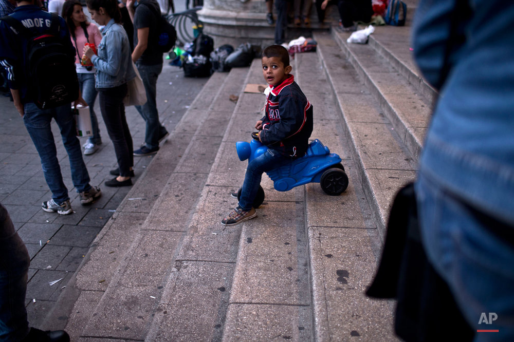 In this photo taken on Saturday, Sept. 5, 2015, a boy rides his tricycle down the stairs of Keleti train station in Budapest, Hungary. Among the hundreds of thousands of migrants making their way to Europe, there are many families whose young children still play or find something to smile about even after harrowing experiences and long journeys. (AP Photo/Marko Drobnjakovic)