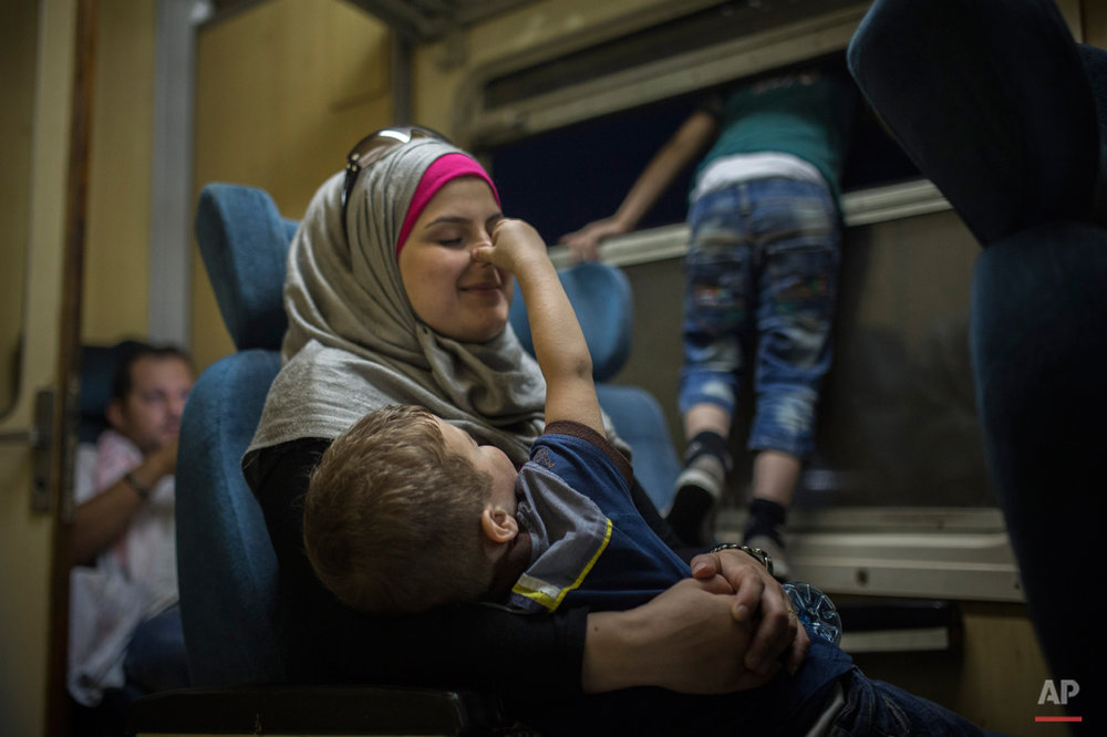 In this photo taken on Monday, Aug. 31, 2015, a Syrian child plays with his mother as they travel by train from Belgrade to the northern Serbian town of Subotica.  Children are resourceful and find joy and distraction for hours in simple objects. Their parents often carry everything they still own in a backpack or two, making dolls and Lego blocks an impossible luxury. (AP Photo/Santi Palacios)