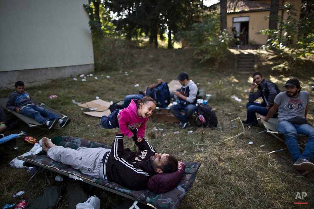 In this photo taken on Friday, Sept. 18, 2015, a Syrian refugee man plays with his daughter after spending the night near an abandoned military barrack in Beli Manastir, near Hungarian border, northeast Croatia. Among the hundreds of thousands of migrants making their way to Europe, there are many families whose young children still play or find something to smile about even after harrowing experiences and long journeys. (AP Photo/Muhammed Muheisen)