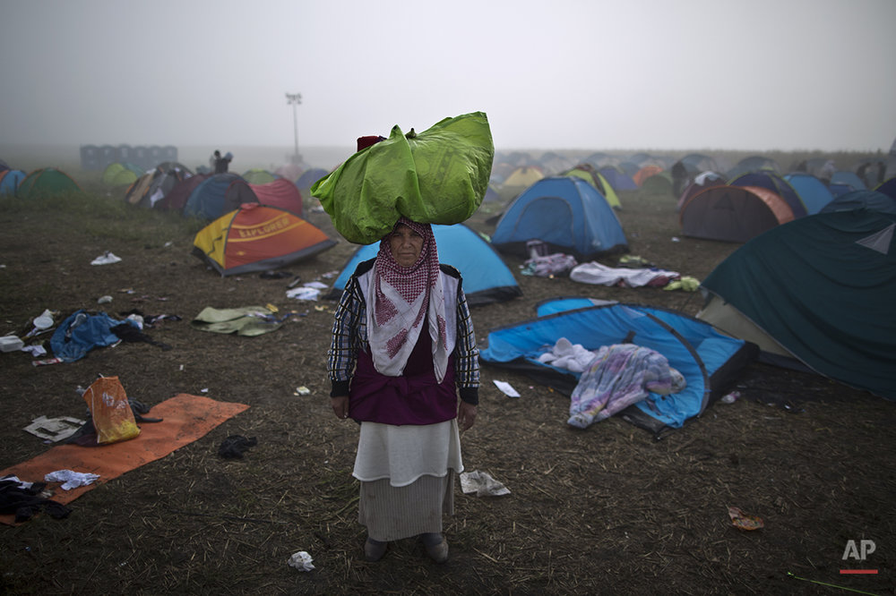 "In this photo taken on Saturday, Sept. 12, 2015, Syrian refugee Sabha Nasser, 62, who came from al-Hasaka, Syria, carries her belongings on her head as poses for a picture, after crossing the Serbian-Hungarian border near Roszke, southern Hungary. ""We had to flee our homes, the shelling is endless. I am old and I need peace. These last 15 days on the road were so humiliating and so miserable I just hope tomorrow will be better,"" she said. (AP Photo/Muhammed Muheisen)"