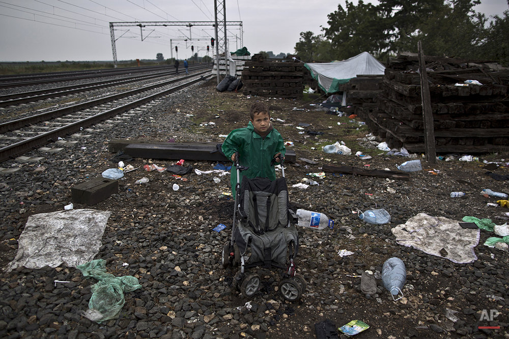 "In this photo taken on Sunday, Sept. 20, 2015, Syrian refugee Radwan Shtaiwi, 8, who came from Deir el-Zour, Syria, poses for a picture while he and his family are hoping to board a train at the station in Tovarnik, Croatia. ""I wish to go to Germany to see my father who had been there for a year, I just want to be with my dad again and my mother is a teacher and I wish she will find work and go to the same school with her,"" he said. (AP Photo/Muhammed Muheisen)"