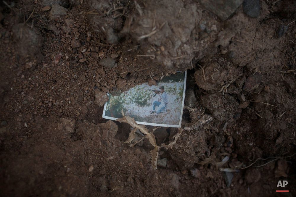In this Monday, Oct. 5, 2015 photo a photograph of a man pointing a fire gun in a wooded area remains left behind next to the road that runs along the north of Greek island of Lesbos. (AP Photo/Santi Palacios)