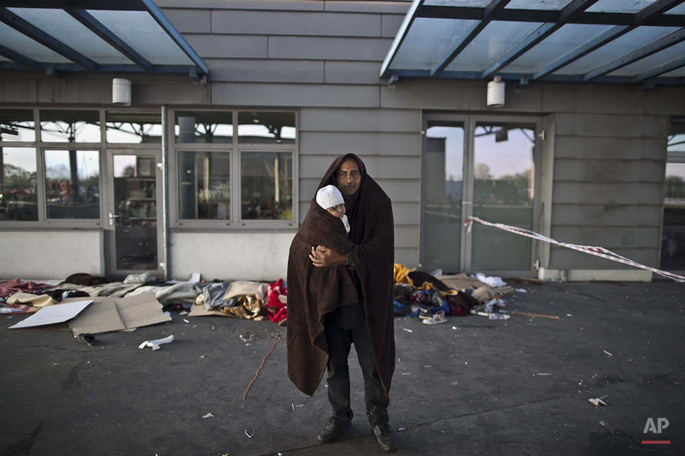 "In this photo taken on Wednesday, Sept. 23, 2015, Syrian refugee Jamal Almasri, 54, who came from Damascus, Syria, wraps himself and his granddaughter with a shawl to shelter from the morning cold as he poses for a picture, after spending the night at a collection point in the truck parking lot of the former border station on the Austrian side of the Hungarian-Austrian border near Nickelsdorf, Austria. Almasri said, ""We met death, we just want to have a life, any life with a rooftop and a shelter. Our lives are over, what matters is the children."" (AP Photo/Muhammed Muheisen)"
