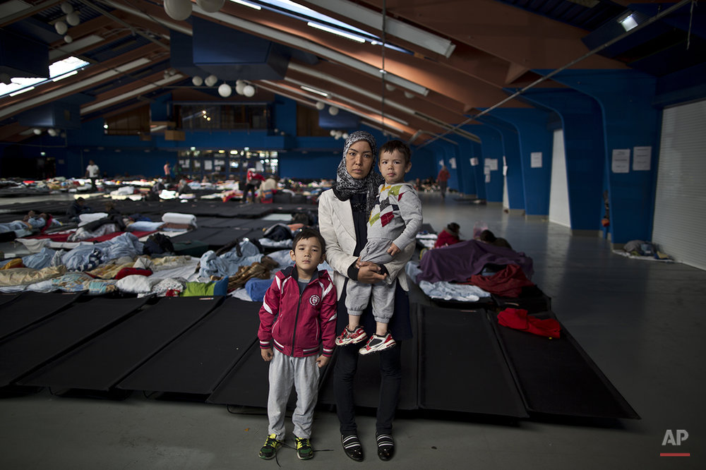 "In this photo taken on Tuesday, Sept. 22, 2015, Iranian Hamideh Salehi, 38, center and her children Ali, 6, left, and Hussein, 2, who came from Mashhad, Iran, pose for a picture in a shelter where they took refuge near Graz, Austria. ""Weeks of walking was very difficult for my children, the cold in the nights, we were hungry and thirsty, we walked for so long and I had to carry my children. I am happy I am here at this shelter in Austria, I dream of freedom and a good education for my kids that's all I want,"" Salehi said. (AP Photo/Muhammed Muheisen)"