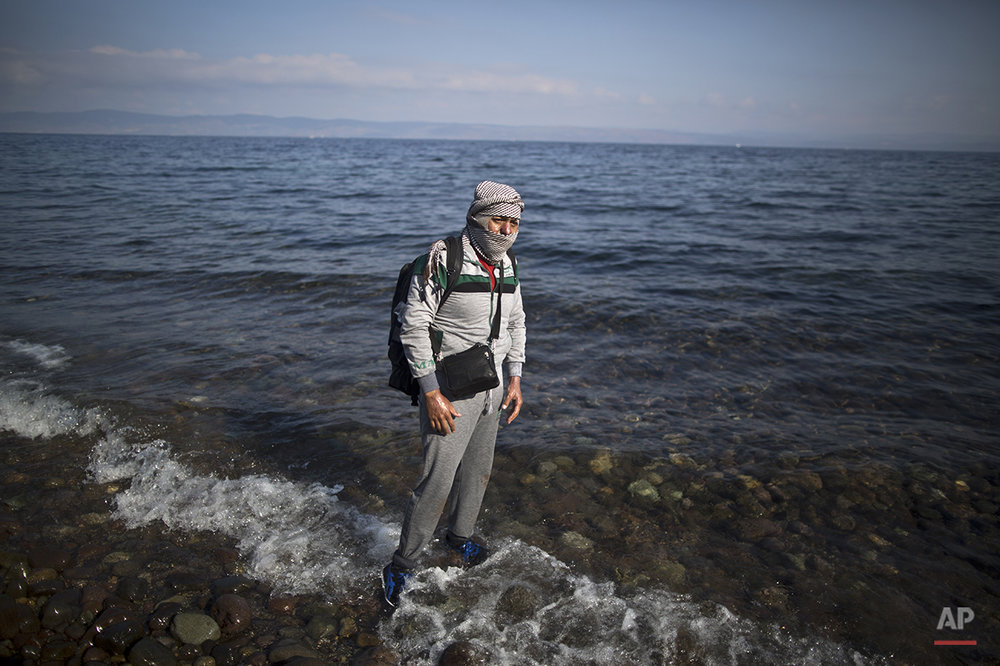"In this photo taken on Saturday, Oct. 3, 2015, Syrian refugee Ala'aldeen Mohammed, 25, who was injured in 2013 in a government bombing that burnt his upper body and face, who came from Aleppo, Syria, poses for a picture shortly after arriving on a dinghy from the Turkish coast to the northeastern Greek island of Lesbos. ""In Germany, they can cure the burns from my injury following a government airstrike in 2013 that I have all over my upper body,"" he said. (AP Photo/Muhammed Muheisen)"
