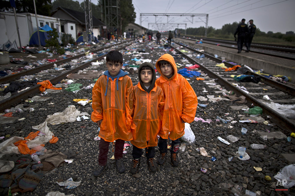 "In this photo taken on Sunday, Sept. 20, 2015, Syrian refugee brothers from right, Sarokan Nasser, 8, Hussam, 6, Ali, 10, who came with their father from al-Hasaka, Syria, pose for a picture while waiting in hope of boarding a train at the station in Tovarnik, Croatia. ""We are going to Germany to join our mother and sister who went a month ago. We just want to grow up in a good country,"" Ali said. (AP Photo/Muhammed Muheisen)"