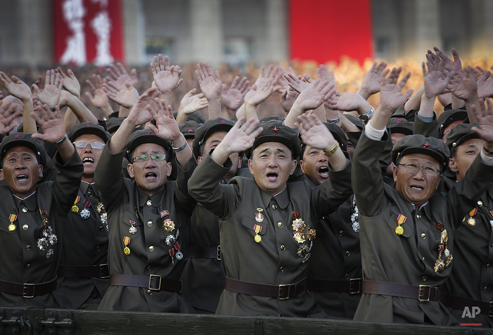 North Korean military soldiers wave as they parade past North Korean leader Kim Jong Un, Saturday, Oct. 10, 2015, in Pyongyang, North Korea. North Korean leader Kim Jong Un declared Saturday that his country was ready to stand up to any threat posed by the United States as he spoke at a lavish military parade to mark the 70th anniversary of the North's ruling party and trumpet his third-generation leadership. (AP Photo/Wong Maye-E)