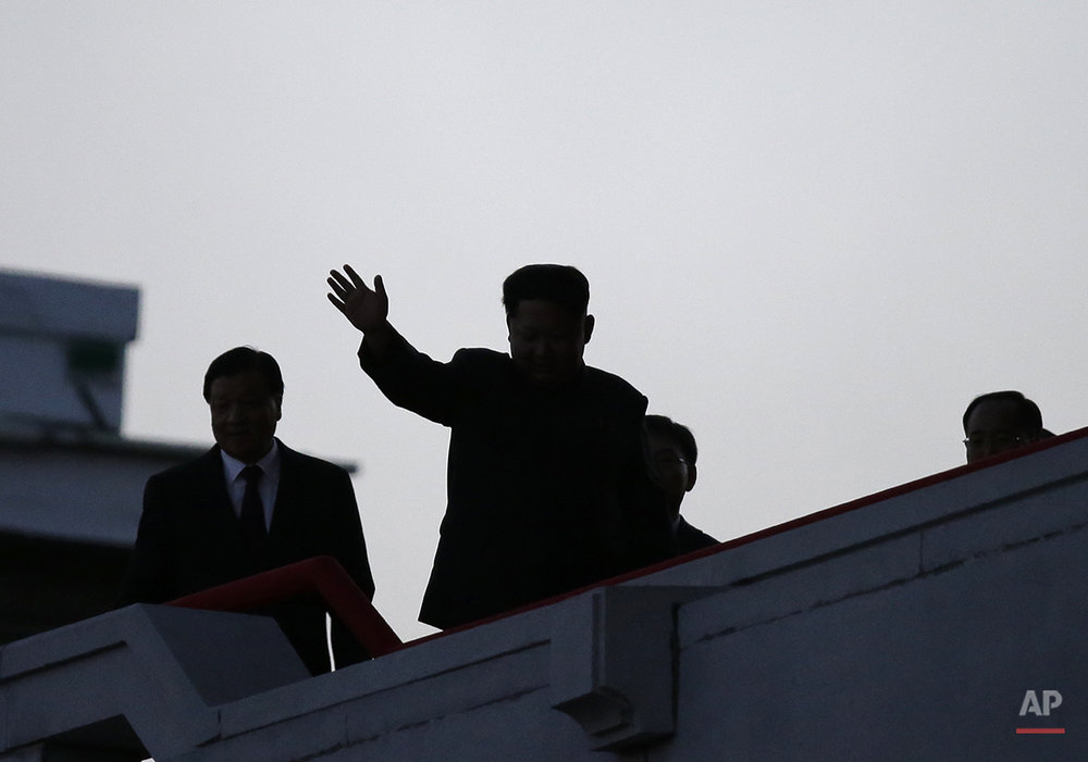 North Korean leader Kim Jong Un, center, is seen in silhouette as he waves at a parade in Pyongyang, North Korea, Saturday, Oct. 10, 2015. North Korean leader Kim Jong Un declared Saturday that his country was ready to stand up to any threat posed by the United States as he spoke at a lavish military parade to mark the 70th anniversary of the North's ruling party and trumpet his third-generation leadership. (AP Photo/Wong Maye-E)