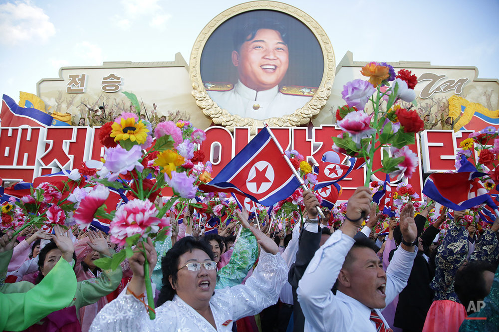 CAPTION CORRECTS THE ID OF MAN IN PORTRAIT TO THE LATE NORTH KOREAN LEADER KIM IL SUNG North Koreans cheer beneath an image of the late North Korean leader Kim Il Sung as they parade in Pyongyang, North Korea, Saturday, Oct. 10, 2015. North Korean leader Kim Jong Un declared Saturday that his country was ready to stand up to any threat posed by the United States as he spoke at a lavish military parade to mark the 70th anniversary of the North's ruling party and trumpet his third-generation leadership. (AP Photo/Wong Maye-E)