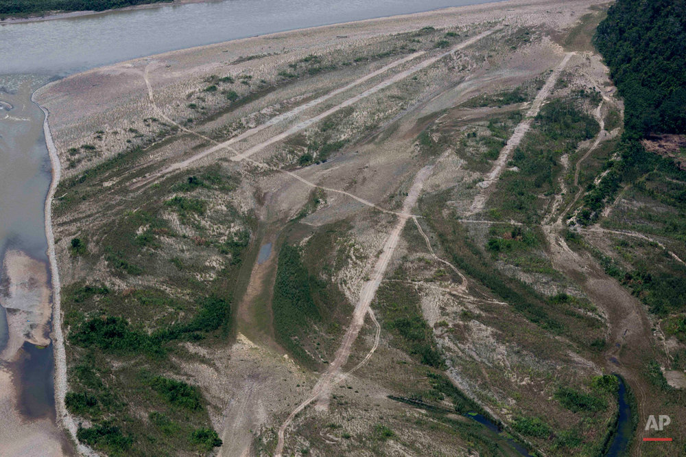 In this Sept. 19, 2014 photo, clandestine airstrips are seen from a military helicopter in the Valley of the Apurimac, Ene and Mantaro River Valleys, or VRAEM, the world's No. 1 coca-growing region, in Pichari, Peru. The area has no radar coverage and the neighboring nations' air forces are limited so drug flights can only be intercepted on the ground. (AP Photo/Rodrigo Abd)