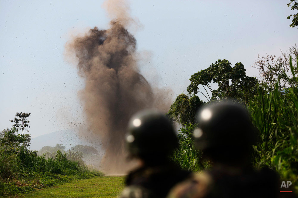 In this Sept. 19 2014 photo, Peruvian counternarcotics forces watch the detonantion of explosives they planted on a part of a clandestine grassy airstrip in the Valley of the Apurimac, Ene and Mantaro River Valleys, or VRAEM, the world's No. 1 coca-growing region in Ayacucho, Peru. Peruvian authorities have launched an operation to destroy clandestine airstrips used by drug traffickers. (AP Photo/Rodrigo Abd)