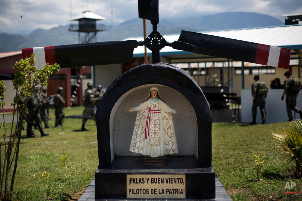 "In this Sept. 19, 2014 photo, a statue of the Virgin Mary stands over a message that reads in Spanish  ""Blades and good wind, Pilots of the Fatherland"" at the Mazamari counter-narcotics military base in the Apurimac, Ene and Mantaro River Valleys, in Junin, Peru. The area, also known as VRAEM, is the world's No. 1 coca-growing region. (AP Photo/Rodrigo Abd)"