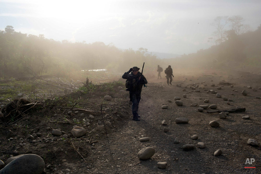 In this Sept. 19, 2014 photo, counternarcotics officers walk in a clandestine airstrip strewn with boulders, in the Apurimac, Ene and Mantaro River Valleys, or VRAEM, the world's No. 1 coca-growing region, in Junin Peru. The boulders are used as a way to camouflage the airstrips from air observation. Security forces say that traffickers pay local villagers to keep the runways hidden and to repair them when they are cratered in counternarcotics operations. (AP Photo/Rodrigo Abd)