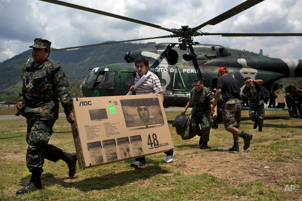 In this, Sept. 19, 2014 photo, soldiers carry a TV after descending from a helicopter at  Mazamari anti drugs military base in the Apurimac, Ene and Mantaro River Valleys, or VRAEM, the world's No. 1 coca-growing region, in Junin, Peru. According to authorities an average of about  4-5 small planes daily fly into Peru from Bolivia, picking up about 300 kilos each of coca paste worth about a third of a million dollars in Bolivia, where it is further refined. (AP Photo/Rodrigo Abd)