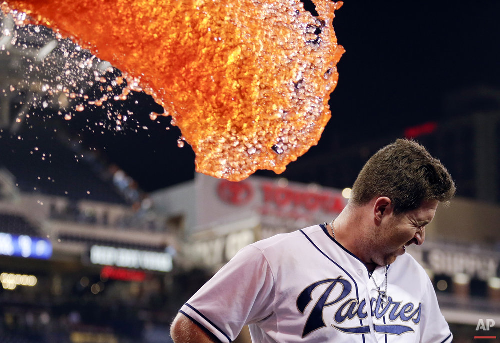 San Diego Padres second baseman Jedd Gyorko braces himself as he is doused in liquid after hitting a walk-off single to defeat the San Francisco Giants in a baseball game Wednesday, Sept. 23, 2015, in San Diego. The Padres won, 5-4. (AP Photo/Gregory Bull)