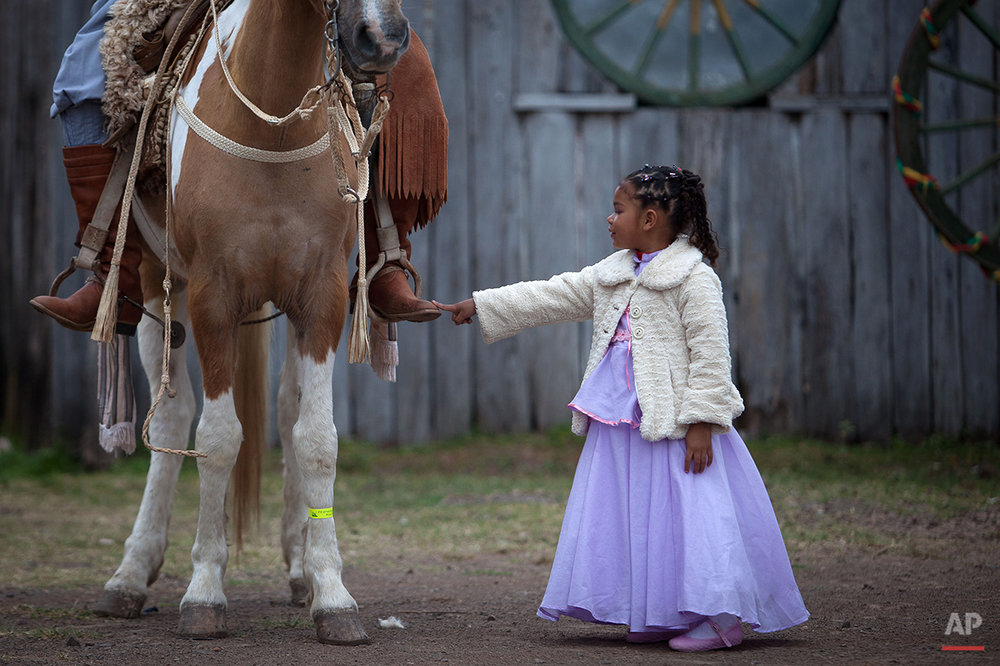 "In this Sept. 20, 2015 photo, girl Alessandra Fortes de Lima, 6, touches the boot of her father Adimir Goncalves de Lima, 49, before a parade during the Semana Farroupilha or ""Ragamuffin"" week, in Alegrete municipality, Rio Grande do Sul state, Brazil. Some of the Brazilian cowboys ride with little girls wearing old-fashioned dresses. They parade before crowds in southern Rio Grande do Sul state, which fancies itself as practically a separate nation, with its rugged rural traditions and Germanic roots. (AP Photo/Eraldo Peres)"