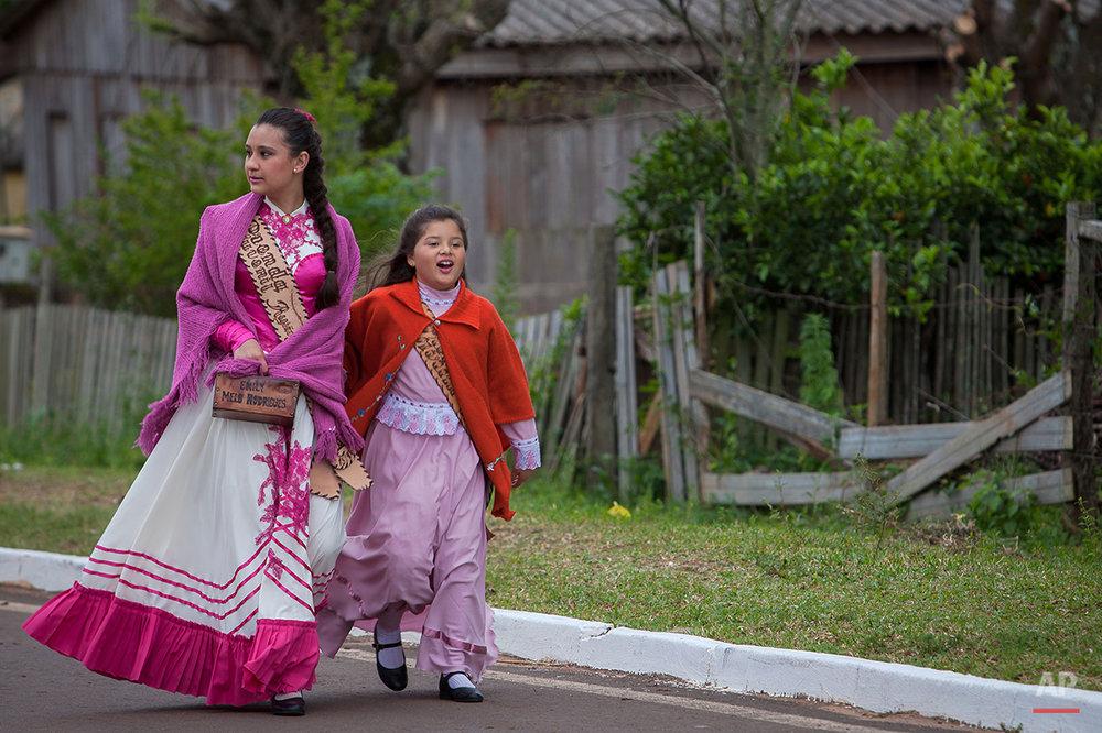 "In this Sept. 19, 2015 photo, girls called ""Prendas"", wear gauchos clothes during the Semana Farroupilha or ""Ragamuffin"" week, in Alegrete municipality, Rio Grande do Sul state, Brazil. Some of the Brazilian cowboys ride with little girls wearing old-fashioned dresses. They parade before crowds in southern Rio Grande do Sul state, which fancies itself as practically a separate nation, with its rugged rural traditions and Germanic roots. (AP Photo/Eraldo Peres)"