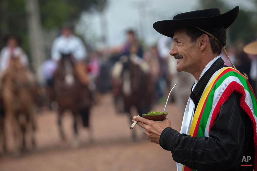 "In this Sept. 19, 2015 photo, gaucho Vanderlei Carvalho, 54, drinks mate during the Semana Farroupilha or ""Ragamuffin"" week, in Alegrete municipality, Rio Grande do Sul state, Brazil. Mate is a traditional South American infused drink, it is prepared by steeping dried leaves of mate herb in hot water and is served with a metal straw from a shared hollow calabash gourd. (AP Photo/Eraldo Peres)"