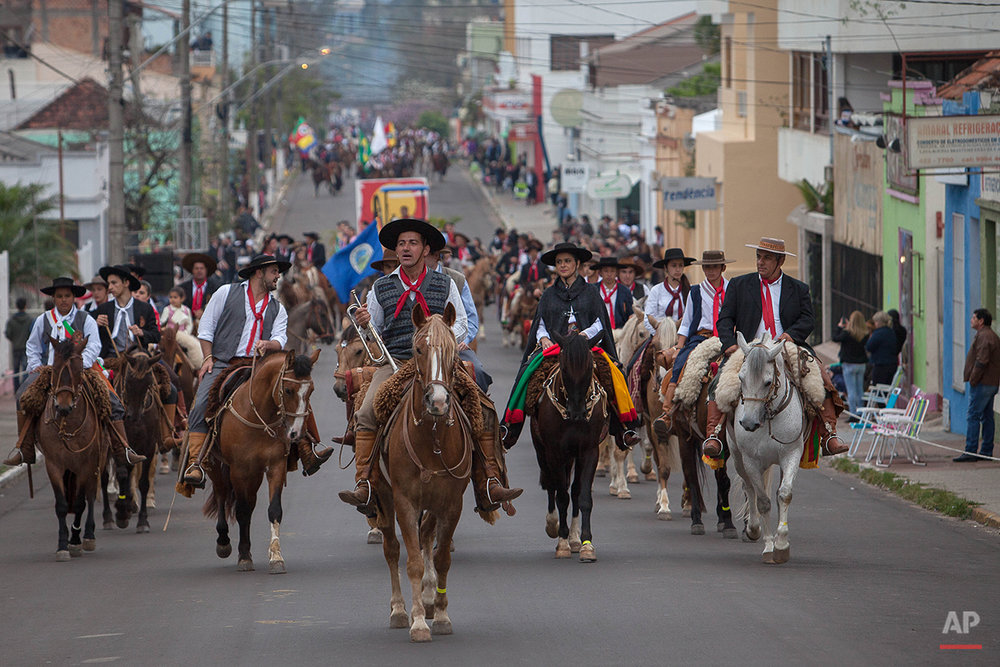 "In this Sept. 20, 2015 photo, gauchos parade during the Semana Farroupilha or ""Ragamuffin"" week, downtown in Alegrete municipality, Rio Grande do Sul state, Brazil. Wearing traditional broad-brimmed hats and red neckerchiefs, their trousers tucked into soft, leather boots, the South American gauchos trot on handsome horses down the street of the small southern community. (AP Photo/Eraldo Peres)"