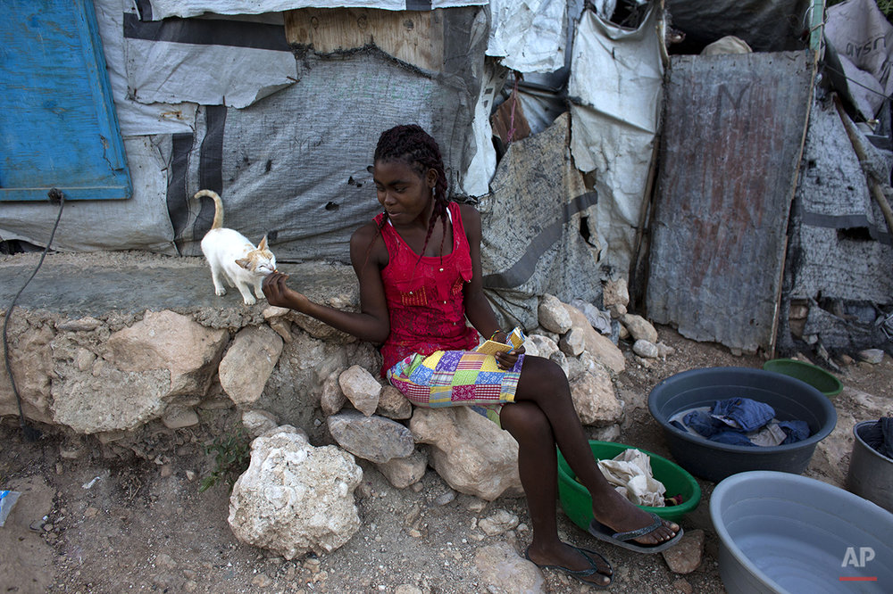 In this June 26, 2015 photo, a young woman shares a cracker with a kitten in a post-earthquake tent camp that residents are hoping to turn into a permanent neighborhood in Port-au-Prince, Haiti. More than five years after a magnitude 7.0 quake destroyed much of the capital, there are few visible signs of the disaster and the vast majority of the people who were displaced have found homes. But there are still tens of thousands of people who have never been able to repair their homes, whose rental subsidies have run out or who never managed to find permanent housing in the first place. (AP Photo/Rebecca Blackwell)