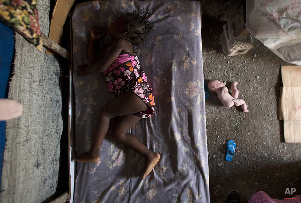 In this June 26, 2015 photo, two-year-old Naika Pierre sleeps on a bed in the dirt-floor tent where she lives with her parents in one of the remaining post-earthquake camps in Cite Soleil, Port-au-Prince, Haiti. When the earthquake struck in 2010, the building where Naika's parents were living in Cite Soleil was heavily damaged and they were forced to move into a tent camp inside the slum. Five years later, they are still living under pieced-together tarps, with cardboard and cinderblocks, the only buffer from a dirt floor that can turn to mud in the rains. (AP Photo/Rebecca Blackwell)
