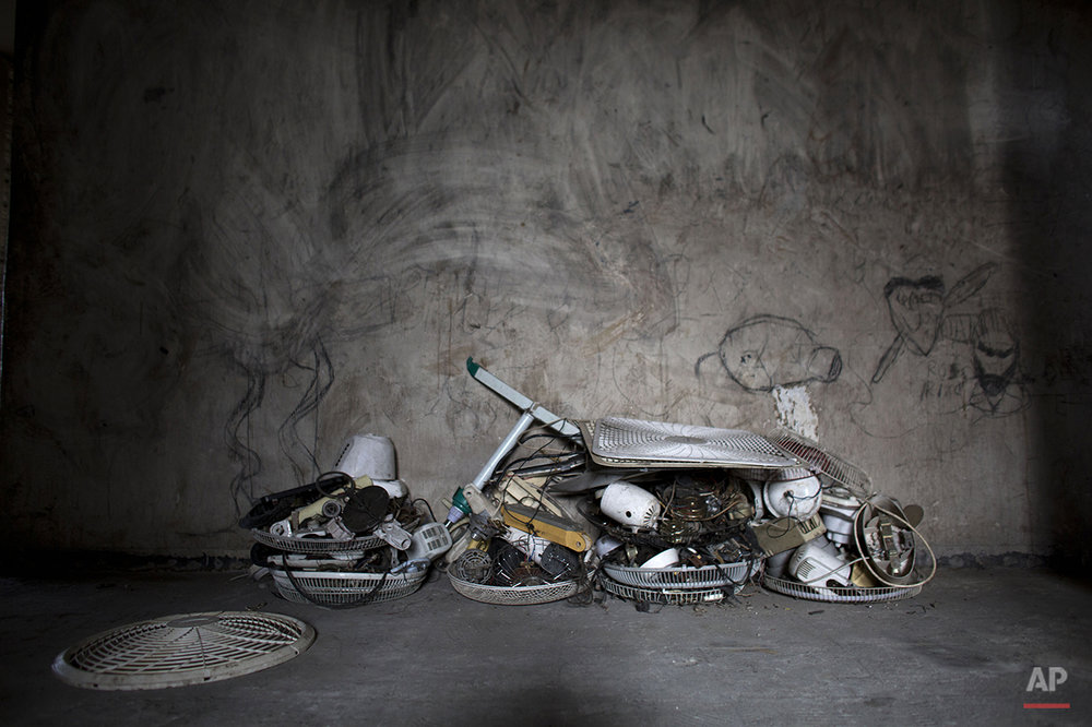 In this June 29, 2015 photo, fan parts recovered by Jimmy Bellefleur sit stacked in the hallway of the abandoned, earthquake damaged government office building where he lives with his family in Port-au-Prince, Haiti. Bellefleur's work as an electrician enables him to buy food and afford relative luxuries such as a double bed and the used televisions and fans he's brought back to life. (AP Photo/Rebecca Blackwell)