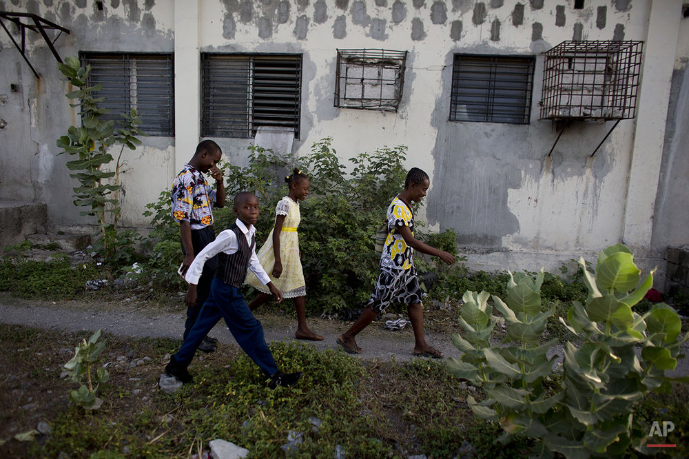In this June 27, 2015 photo, Johnly Clif Gaspard, back left, heads to Sunday morning Mass with his mother and two younger siblings, as they leave the abandoned shipping depot where they live in Port-au-Prince, Haiti. Although his mother works full-time in a button factory and Gaspard earns money selling motorized toys built from scrap materials, the family cannot afford to move out of the depot where they are squatting along with five other families. (AP Photo/Rebecca Blackwell)