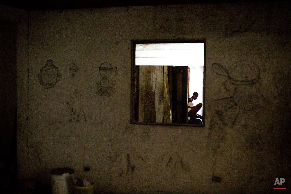 In this June 26, 2015 photo, single mother Manushka Doneis, 18, sits inside the abandoned shipping company building where she lives with her siblings and five-month-old daughter in Port-au-Prince, Haiti. Haitians who are homeless since the 2010 earthquake can be found living in the best conditions they can find _ the ruins of a luxury hotel, makeshift shelters on the grounds of the destroyed national theater, and even in one case in an unventilated trailer. (AP Photo/Rebecca Blackwell)