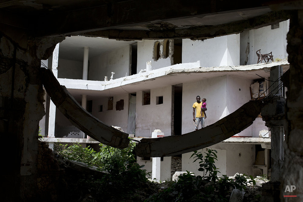 In this June 29, 2015 photo, single father Jean Donalson Tousena Bagui holds his two-year-old daughter outside their room at the earthquake-damaged Hotel Le Palace in central Port-au-Prince, Haiti. Tousena Bagui said he was a security guard at the hotel before the 2010 earthquake and stayed on as a self-appointed caretaker. He receives no compensation, he said, and has not received word from the hotel's owner on what will become of the site. (AP Photo/Rebecca Blackwell)