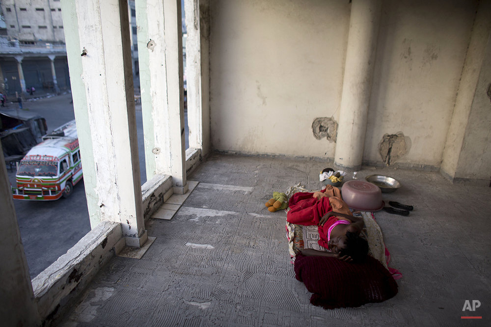 In this June 29, 2015 photo, Zarmor Sendi sleeps in an open room inside an abandoned, earthquake damaged government office building where she's living in Port-au-Prince, Haiti. During the day, Sendi inhabits one of the building's former bathrooms, too small to lie down in, and protected only by a thin curtain. Although the building's residents all know each other, there is no way to secure the site, leaving children and single women like Sendi particularly vulnerable. (AP Photo/Rebecca Blackwell)