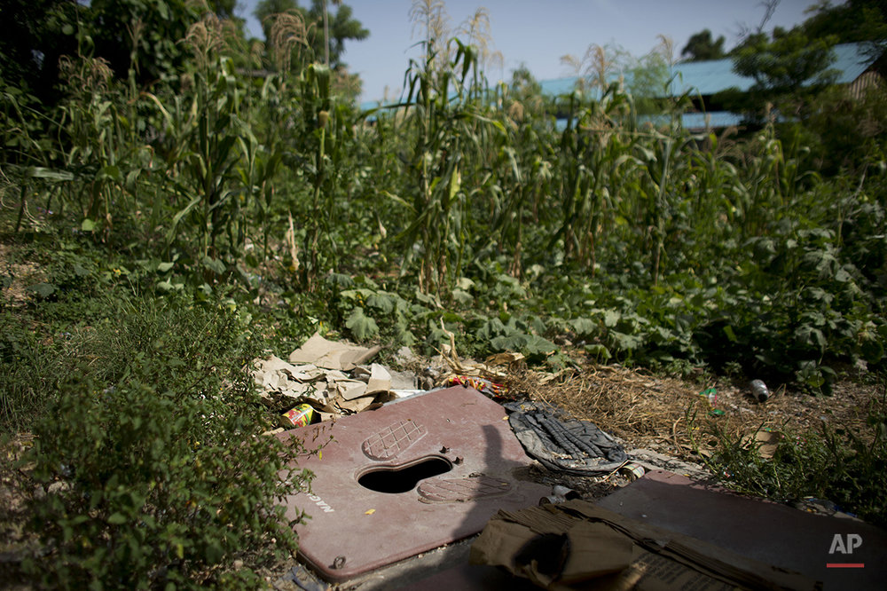 In this June 29, 2015 photo, a makeshift squat toilet installed over a shallow pit serves families living in and around damaged buildings behind the ruins of the National Theater, in central Port-au-Prince, Haiti. Sanititation is a problem in camps and squatter settlements alike. Many people live without access to any toilet facilities, and water for drinking and washing must be bought in by the bucket. (AP Photo/Rebecca Blackwell)
