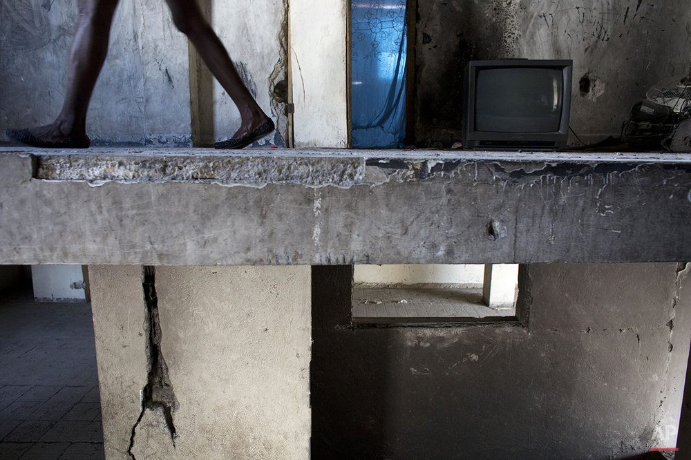 In this June 29, 2015 photo, Zarmor Sendi walks along the stairwell of the abandoned, earthquake damaged government building where she's living in Port-au-Prince, Haiti.  Sendi, 28, lost her home in the quake and was later evicted from a camp set up for those displaced by the quake. (AP Photo/Rebecca Blackwell)