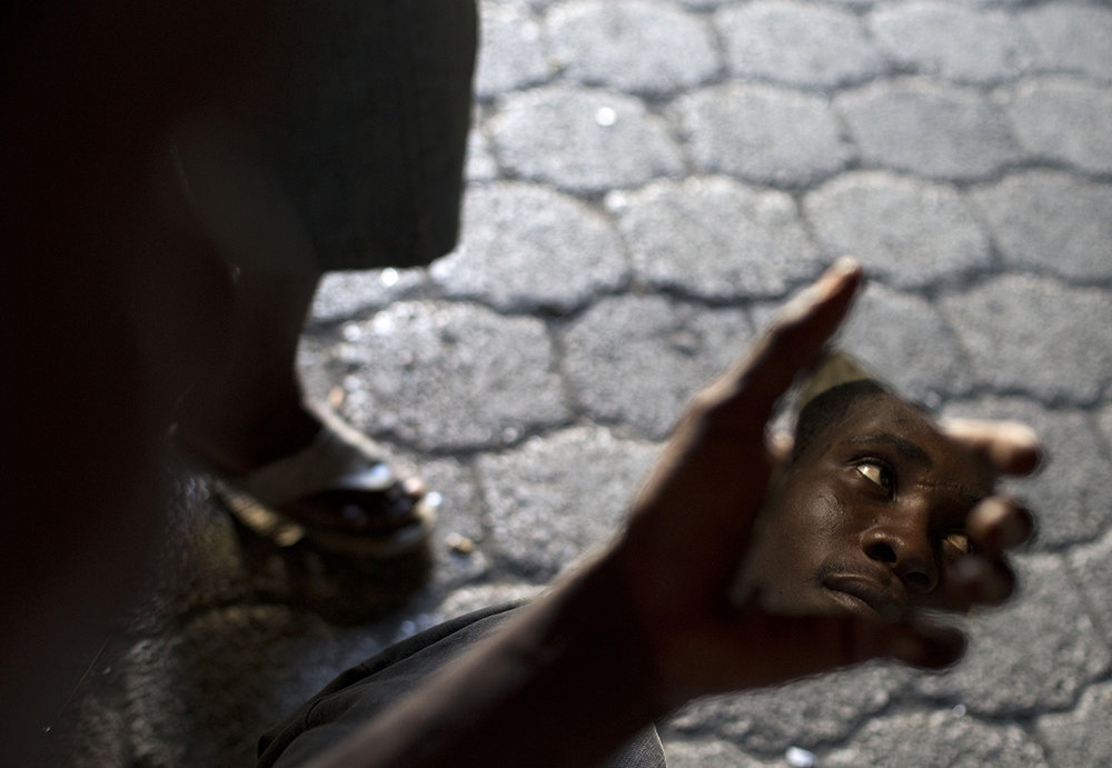 In this June 27, 2015 photo, a man uses a shard of mirror to check his reflection as he passes the time with other residents inside the abandoned shipping depot where they live in Port-au-Prince, Haiti. Some residents of the building have full-time jobs, while others are partially-employed or look for day work. (AP Photo/Rebecca Blackwell)