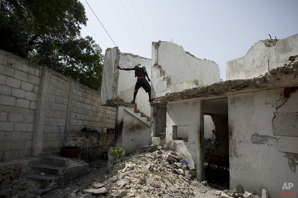 In this June 29, 2015 photo, a resident of the earthquake-damaged Hotel Le Palace makes his way downstairs from the room he inhabits in central Port-au-Prince, Haiti. Though much of the hotel was destroyed, some of the guest rooms, which still have intact walls, have become homes to people displaced by the quake. The ruined hotel has no running water or working sanitary facilities. (AP Photo/Rebecca Blackwell)