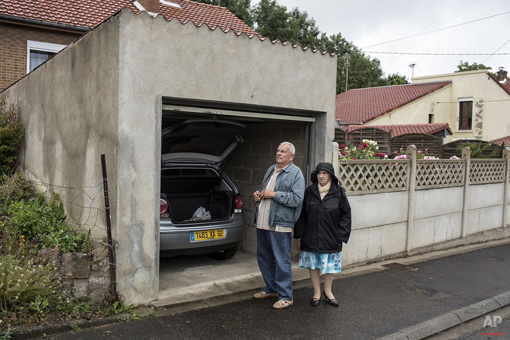 A couple stand outside of their garage as they wait for the race to pass during the fifth stage of the 102nd edition of the Tour de France, between Arras and Amiens, France, Wednesday, July 8, 2015. (AP Photo/Laurent Cipriani)