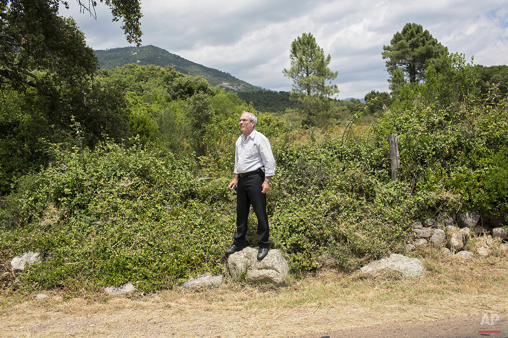 A man stands on a rock on the side of the road to watch the the first stage of the 100th edition of the Tour de France, between Porto-Vecchio and Bastia, France, Saturday, June 29, 2013. (AP Photo/Laurent Cipriani)