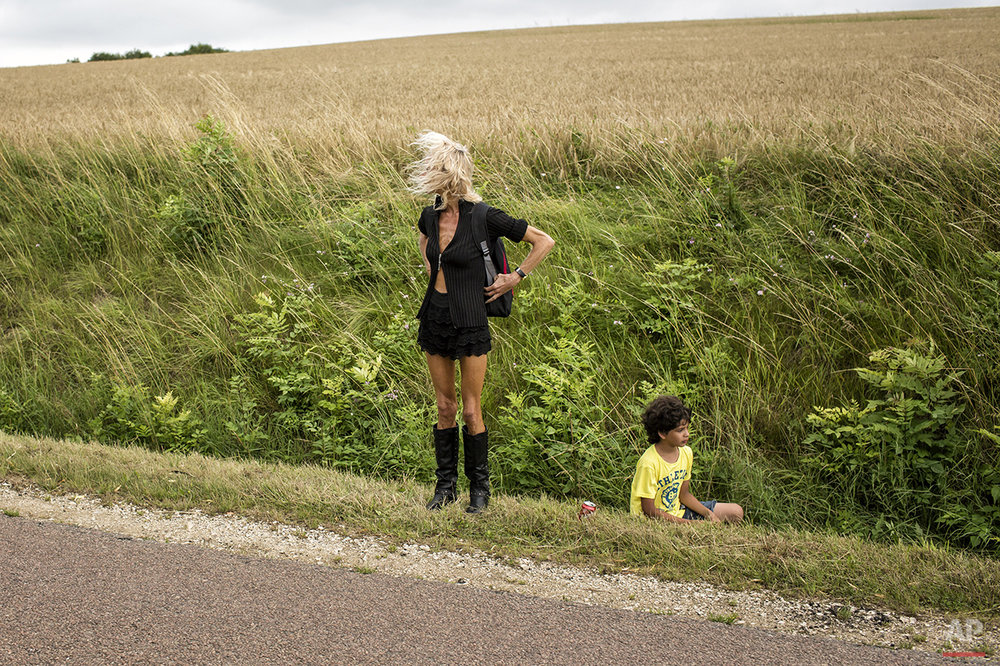 A woman and young boy stand on the side of the road waiting for the arrival of competitors during the seventh stage of the 101st edition of the Tour de France, between Epernay and Nancy, France, Friday, July 11, 2014. (AP Photo/Laurent Cipriani)