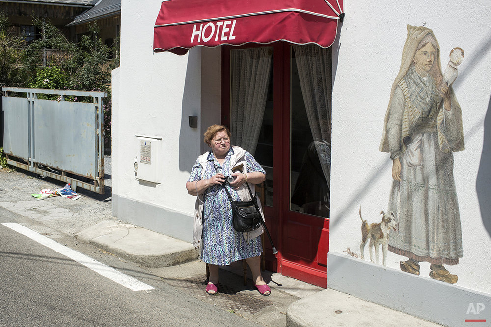 A woman stands on the side of the road outside of a hotel during the eleventh stage of the 102nd edition of the Tour de France, between Pau and Vallee de Saint-Savin, France, Wednesday, July 15, 2015. (AP Photo/Laurent Rebours)