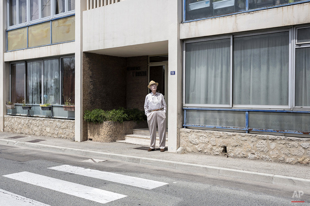 A man stands outside of his apartment as he waits for the fifth stage of the 100th edition of the Tour de France, between Cagnes-sur-Mer and Marseille, France, Wednesday, July 3, 2013. (AP Photo/Laurent Cipriani)