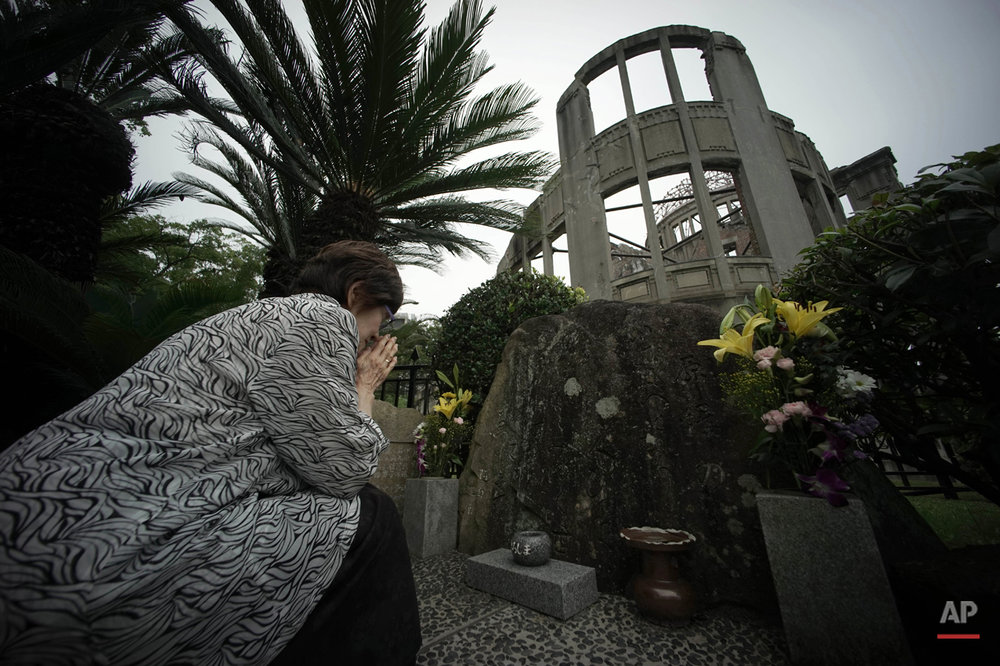 In this July 3, 2015 photo, Kimie Mihara, a survivor of the 1945 atomic bombing, prays at the cenotaph at the Atomic Bomb Dome, as it is known today in Hiroshima, Hiroshima Prefecture, southern Japan. Built in 1915, the dome building was a rare example of Western architecture in Hiroshima at the time. Czech architect Jan Letzel designed it to be a city landmark and an exhibition hall for industrial and cultural promotion. Mihara was a worker at a government office in the dome building in 1945. (AP Photo/Eugene Hoshiko)