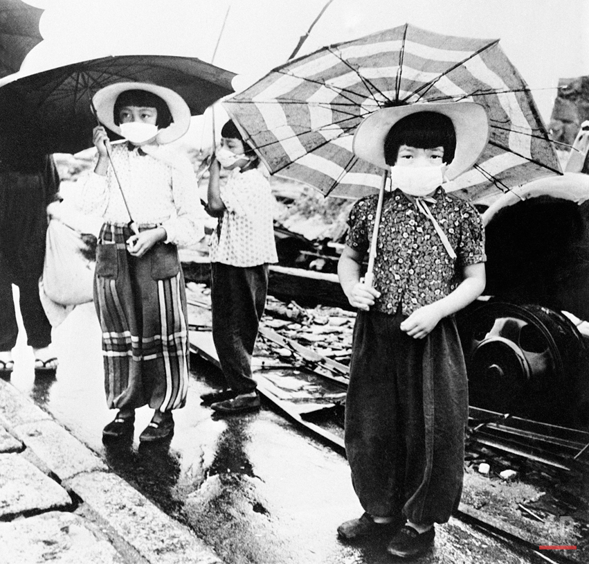 The Japanese of atom-bombed Hiroshima have put the ancient custom of wearing nose and mouth masks while out of doors to a good use. Hiroshima was the first town to be hit by an atom bomb during the war. Japanese girls wearing their masks as they walk through the devestated streets of Hiroshima, Japan, on Oct. 6, 1945. (AP Photo)