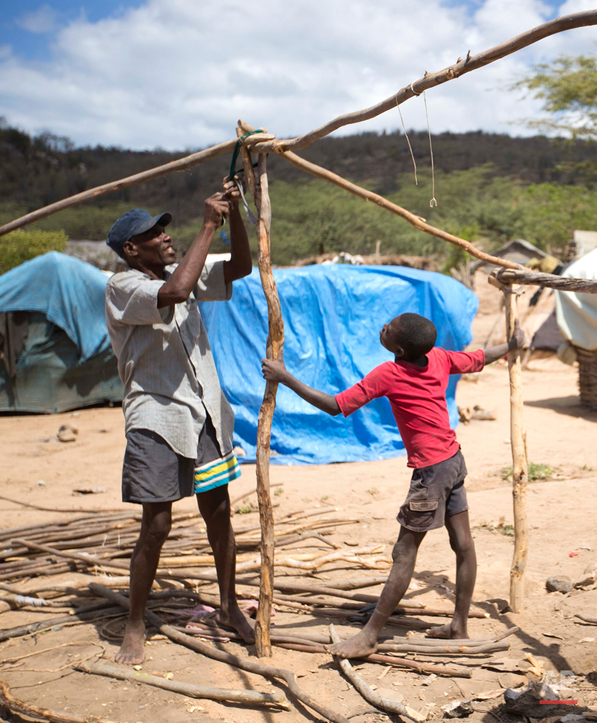 In this Aug. 3, 2015 photo, Haitian Elissene Jean Louis, 61, builds his family's makeshift home with help from his son Edez at an encampment set up by Haitians who left the Dominican Republic, in Anse-a-Pitres, Haiti. Jean Louis' family fled the D.R. by foot after threats from locals, and now lives here with approximately 700 families who are cut off from the jobs that sustained them in the D.R. (AP Photo/Dieu Nalio Chery)